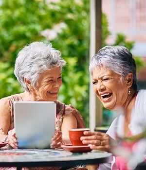 Older Adults Socializing With Tablet In Hand