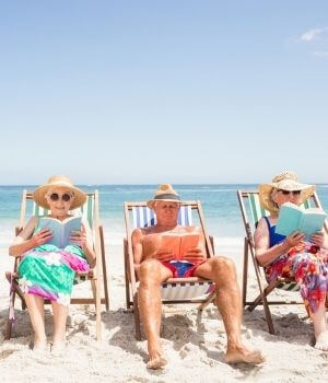 Older Adults Reading On The Beach