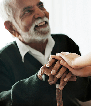 Older Male Adult Smiling Holding Child's Hands