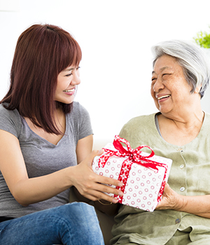 senior and caregiver exchanging holiday gifts