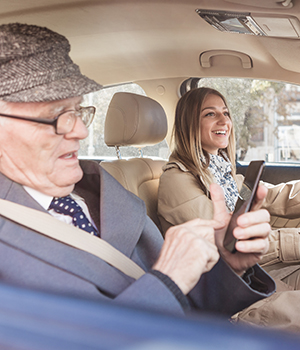 Senior and caregiver driving in car