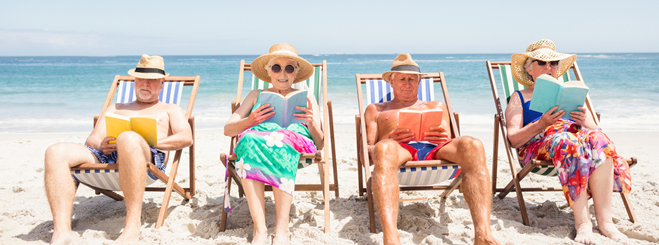 Older adults reading on beach