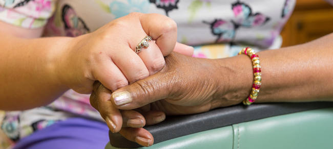 nurse and senior PACE participant hold hands